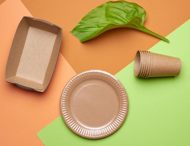 Utensílios de papel descartáveis de papel artesanal marrom e materiais reciclados em um fundo verde alaranjado