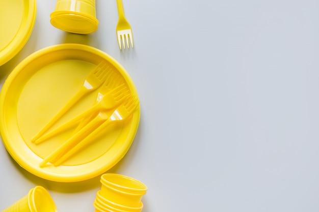 Utensílios de piquenique amarelo de uso único para reciclagem em cinza.