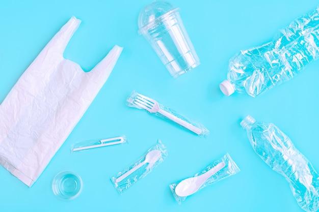 Utensílios de plástico sobre fundo verde. conceito de utilização de plástico de reciclagem
