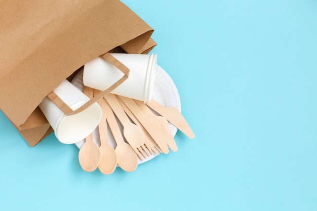 Utensílios descartáveis eco-amigáveis feitos da madeira de bambu no saco de papel no azul.