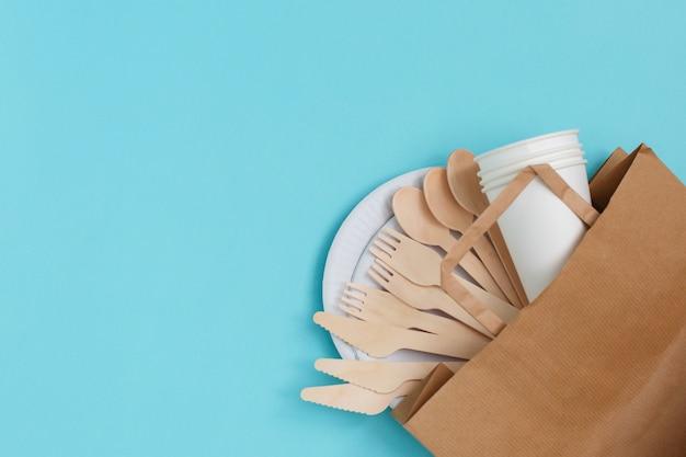 Utensílios descartáveis eco-amigáveis feitos da madeira de bambu sobre o saco de papel no azul.