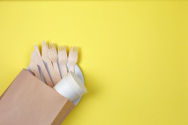 Utensílios descartáveis eco-amigáveis feitos da madeira e do papel de bambu no fundo amarelo.