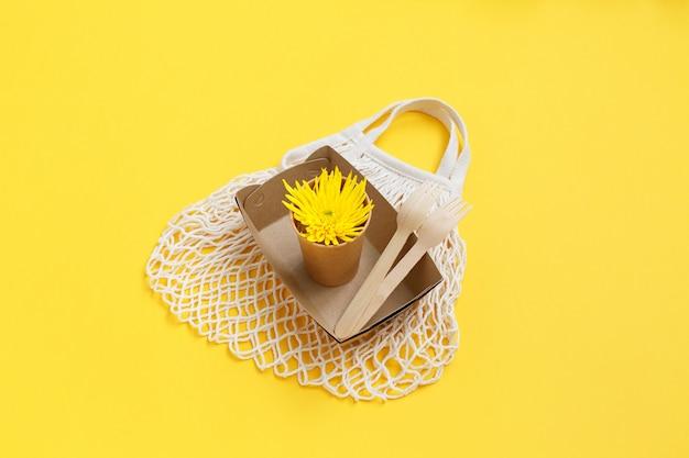 Utensílios descartáveis ecológicos e saco de têxteis de malha na parede amarela