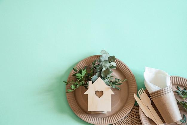 Utensílios descartáveis ecológicos feitos de madeira de bambu e papel em um fundo de tendências.