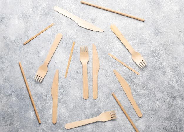 Utensílios descartáveis ecológicos feitos de madeira de bambu e papel sobre um fundo azul. colheres drapeadas, garfo, facas, tigelas de bambu com copos de papel.