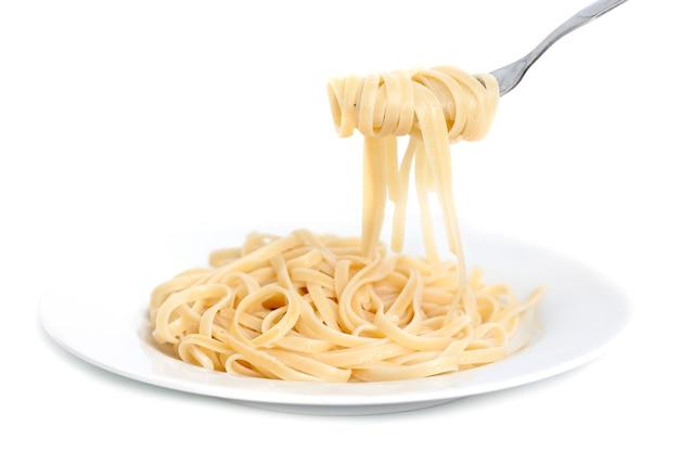 Utensílios pegando o espaguete do prato.