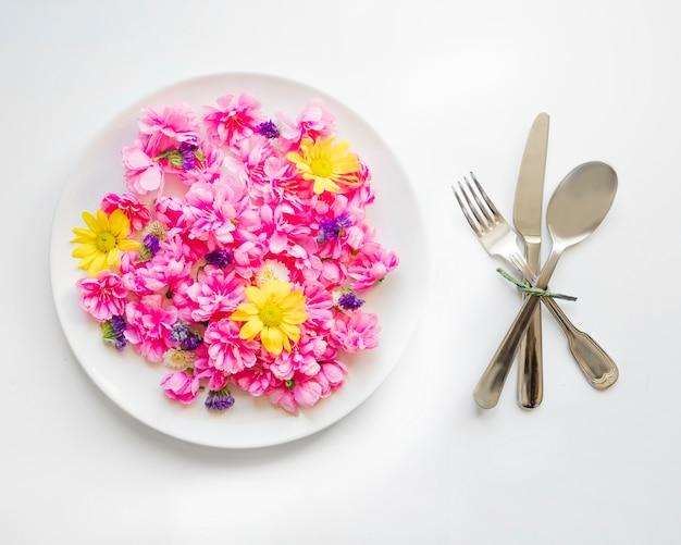 Utensílios perto de flores bonitas no prato
