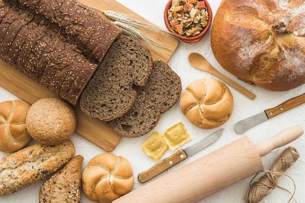 Utensílios perto de pão e pãezinhos