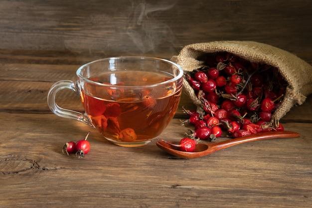 Útil para o chá saudável da rosa selvagem na superfície da madeira, fruto da rosa brava no saco.