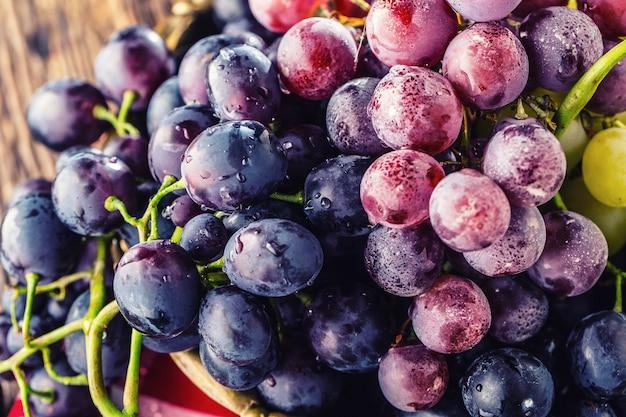 Uva. cacho de uvas multicoloridas em tigela retrô na velha mesa de carvalho.