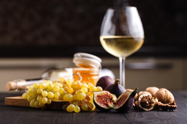 Uva, figos e mel com um copo de vinho branco sobre fundo de madeira