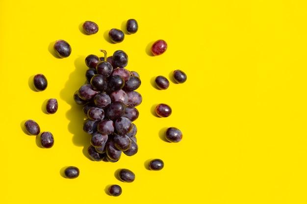 Uva fresca na superfície amarela