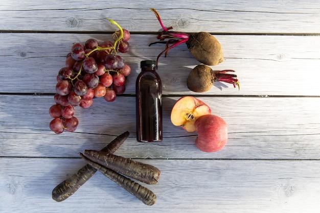 Uva ou vinho uva com maçã, laranja e beterraba prensada em suco de uva saudável em uma garrafa em uma placa de madeira