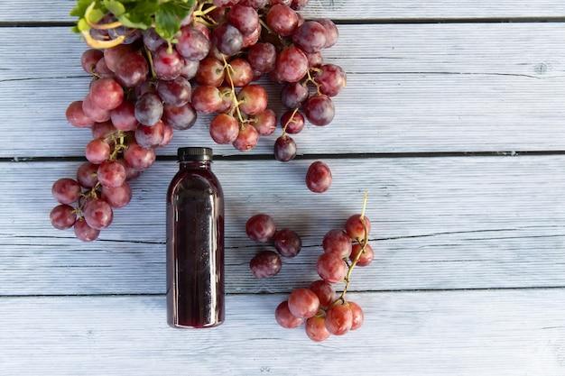 Uva ou vinho uva comprimida em suco de uva saudável em uma garrafa em uma placa de madeira