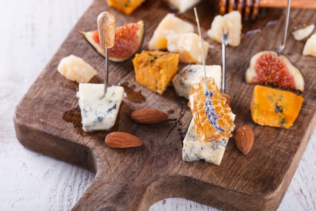 Uva, queijo, figos e mel com um copo de vinho tinto e branco em uma placa de madeira