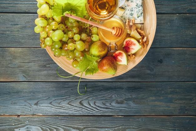 Uva, queijo, figos e mel com vinho na mesa de madeira
