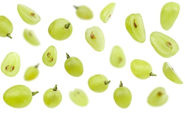 Uva verde caindo isolada no foco seletivo de fundo branco
