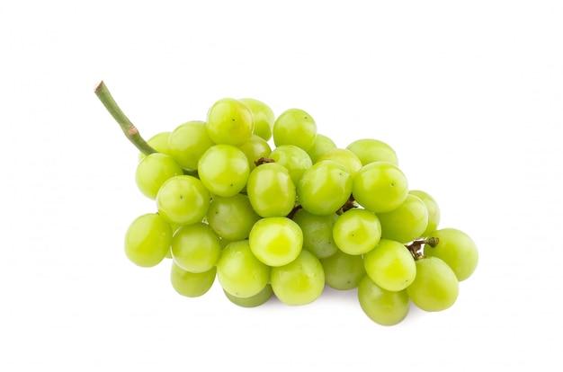 Uva verde com as folhas isoladas no branco.