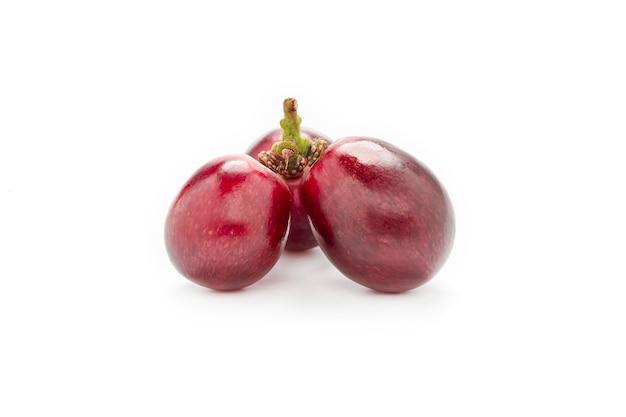 Uva vermelha fresca isolada no fundo branco.