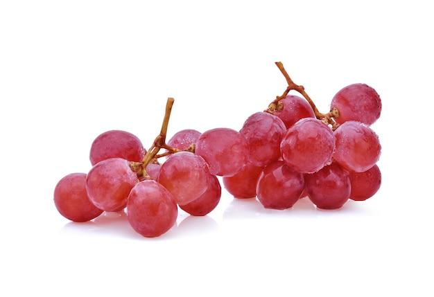 Uva vermelha madura com gotas isoladas em branco.