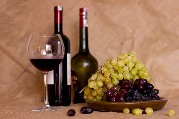 Uvas azuis e verdes em um prato marrom da argila. garrafa com vermelho e