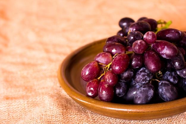 Uvas azuis em um prato de barro marrom