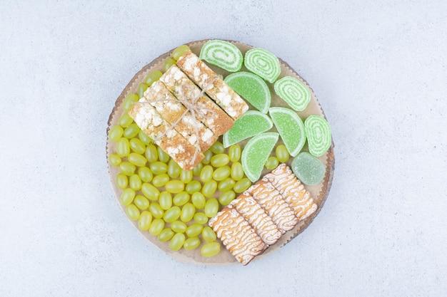 Uvas, biscoitos e marmeladas na placa de madeira.