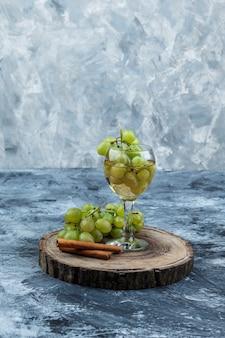 Uvas brancas de close-up, canela, copo de uísque na placa de madeira no fundo de mármore azul escuro. vertical