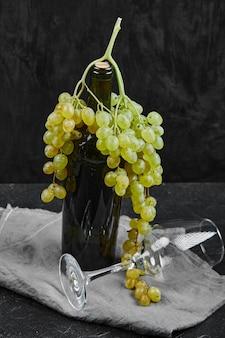 Uvas brancas em volta de uma garrafa de vinho e um copo vazio em uma superfície escura com uma toalha de mesa cinza