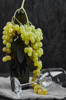Uvas brancas em volta de uma garrafa de vinho e um copo vazio na superfície escura