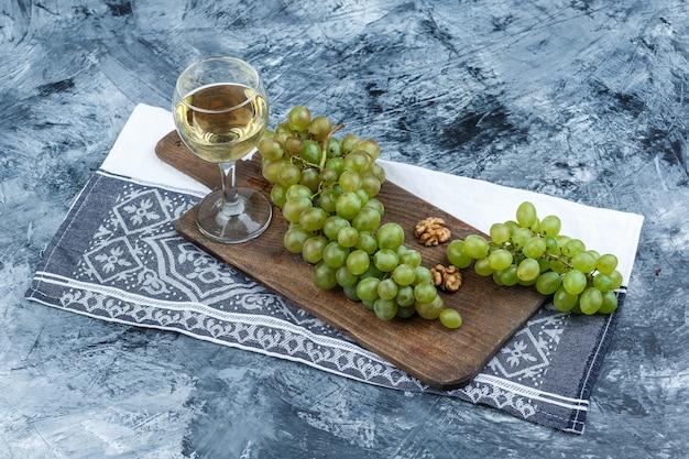 Uvas brancas, nozes em uma tábua de cortar com toalha de cozinha, copo de uísque com vista de alto ângulo em um fundo de mármore azul escuro