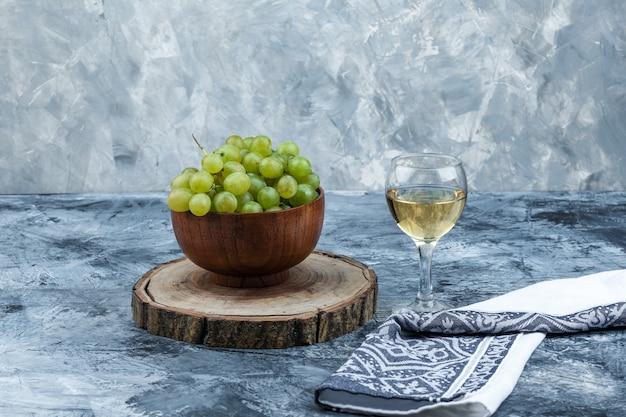 Uvas brancas, nozes em uma tábua de cortar com um copo de uísque, close-up de toalha de cozinha em um fundo de mármore azul claro e escuro