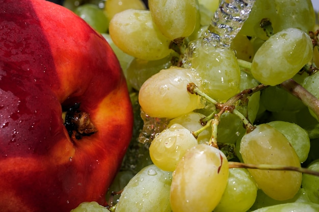 Uvas brancas sem sementes em um cacho e nectarina sob um fluxo de macro fotografia em close-up de água limpa