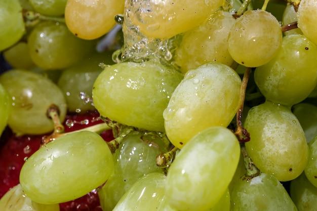 Uvas brancas sem sementes em um cacho sob um fluxo de macrofotografia em close-up de água limpa