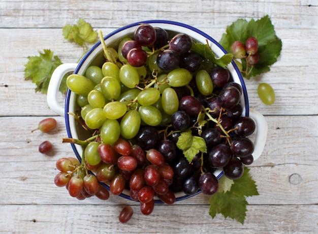 Uvas brancas, vermelhas e azuis em uma tigela na mesa de madeira