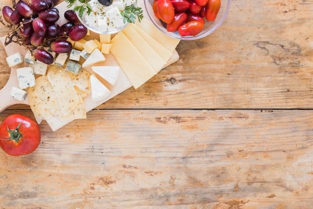 Uvas, cerejas tomate e queijo na mesa de madeira