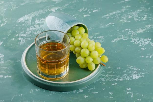 Uvas com bebida em um copo no fundo de gesso e bandeja, vista de alto ângulo.