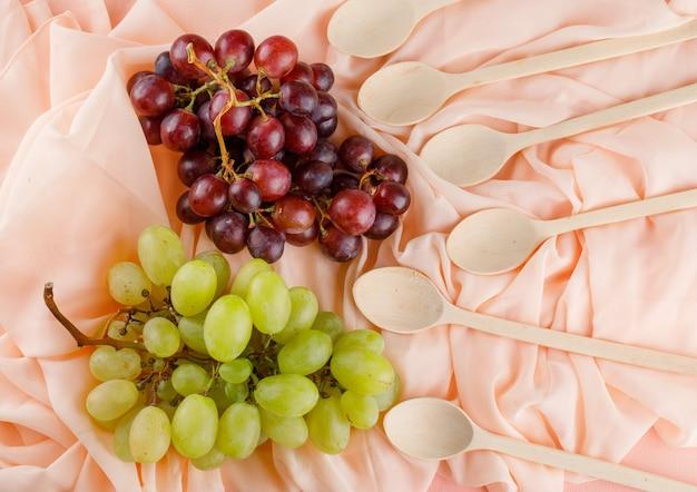 Uvas com colheres de madeira espalmadas sobre um tecido rosa