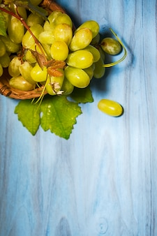 Uvas com folhas no fundo madeira