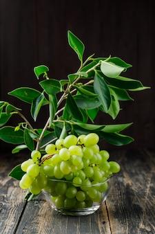Uvas com folhas no ramo em uma tigela de vidro na superfície de madeira, vista lateral.