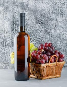 Uvas com garrafa de bebida em uma cesta em gesso e suja, vista lateral.