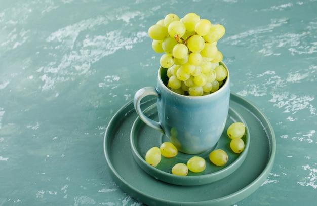 Uvas com prato na xícara e pires em fundo de gesso, vista de alto ângulo.