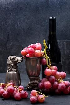 Uvas cor de rosa em um copo de metal vintage em um fundo preto e uma garrafa