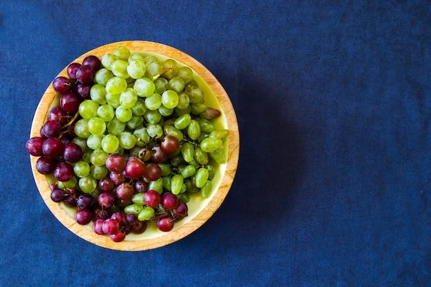 Uvas de outono na mesa azul, colhendo frutas da estação
