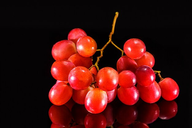 Uvas-de-rosa maduras em fundo preto