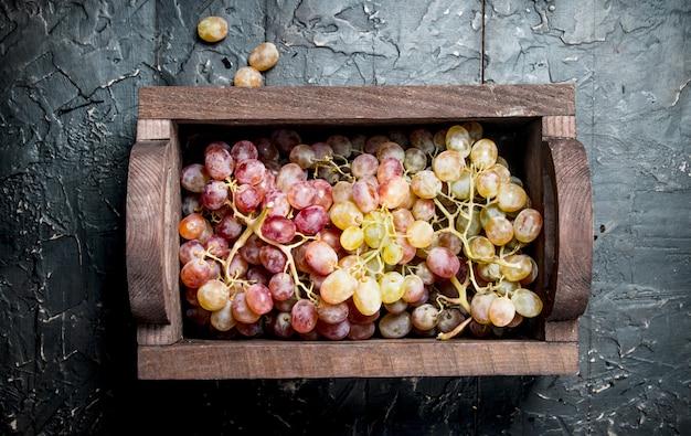 Uvas-de-rosa na caixa na mesa rústica.
