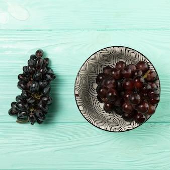 Uvas deliciosas na tigela sobre fundo de madeira