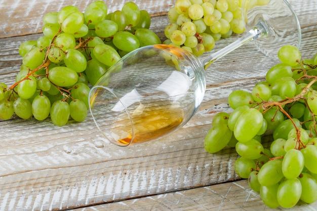 Uvas doces com vista de alto ângulo da bebida em um fundo de madeira