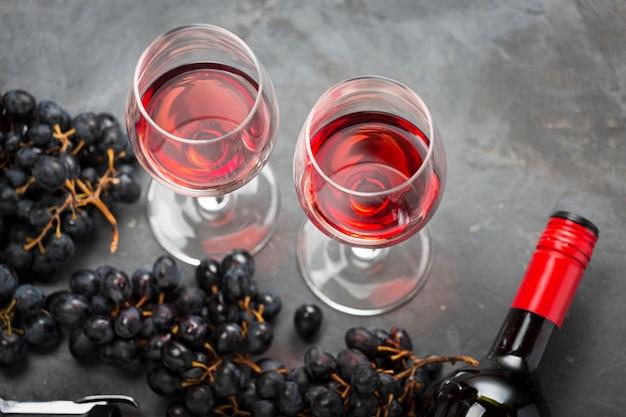Uvas e copos de vinho tinto