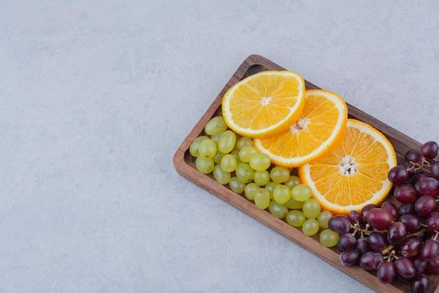 Uvas e fatias de laranja na placa de madeira. foto de alta qualidade